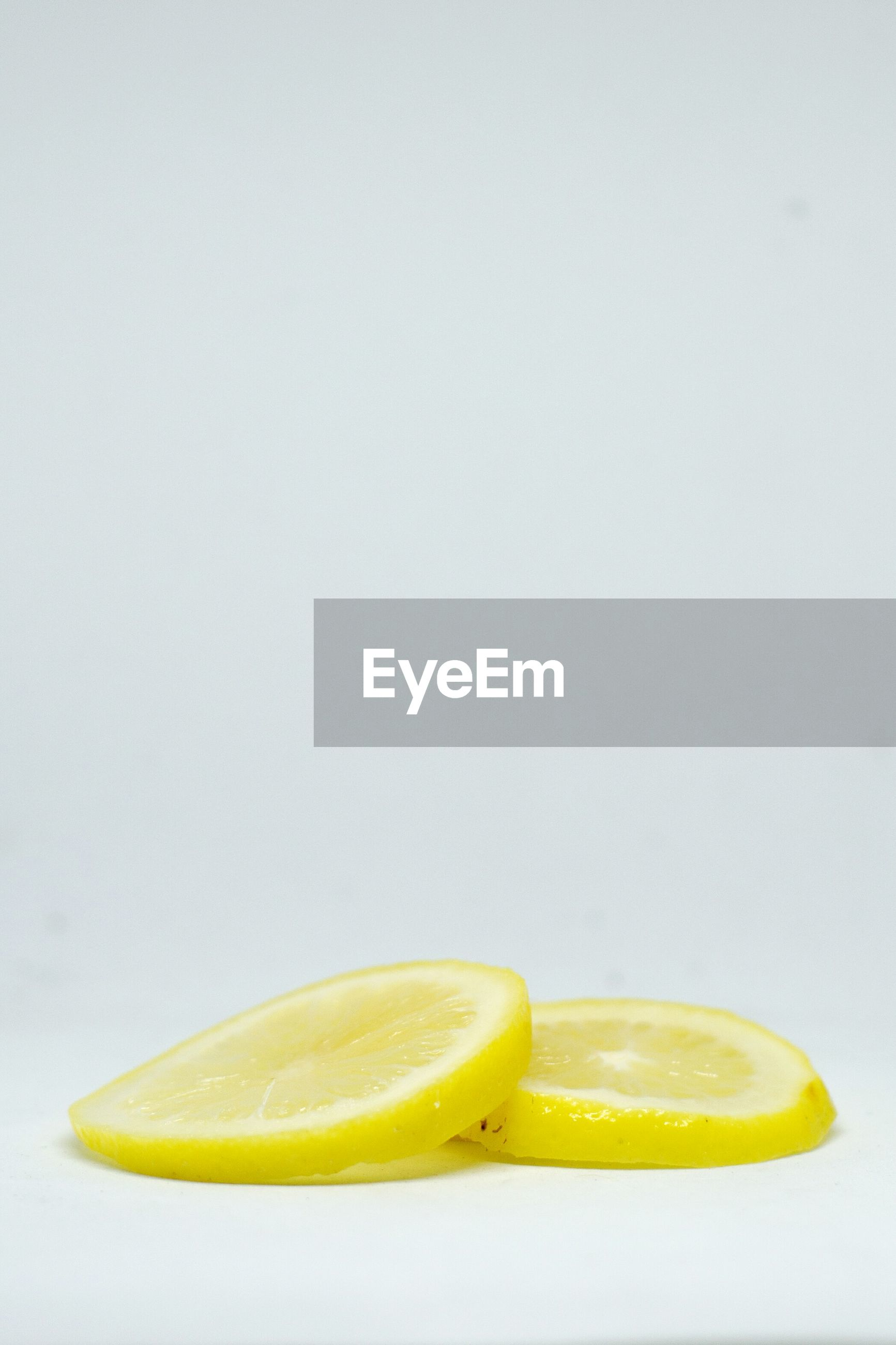 CLOSE-UP OF LEMON AGAINST WHITE BACKGROUND