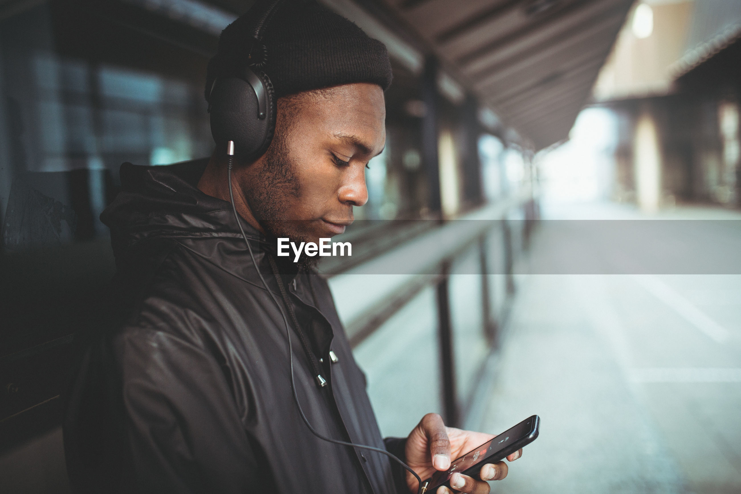Man listening music on headphones while leaning on window