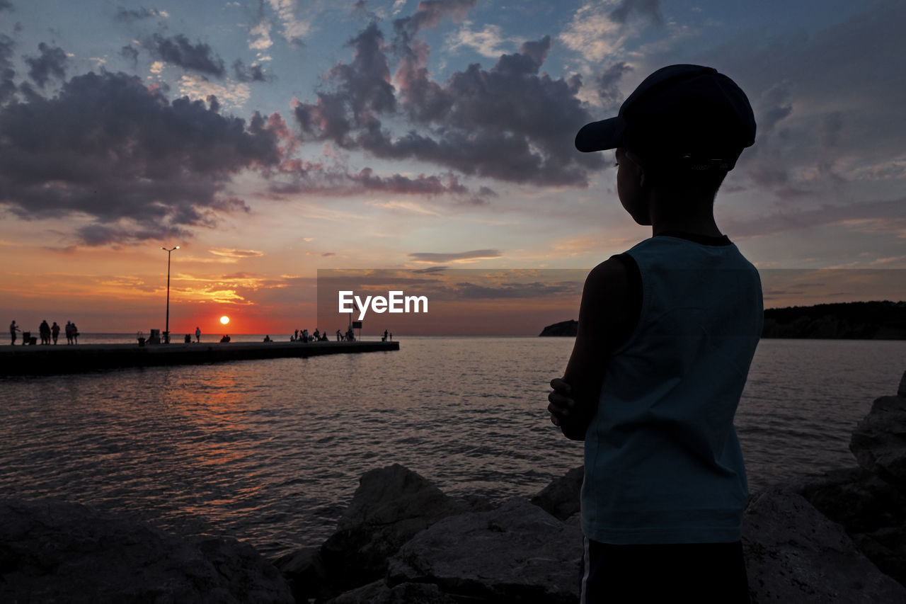 Boy looking at sea against sky during sunset