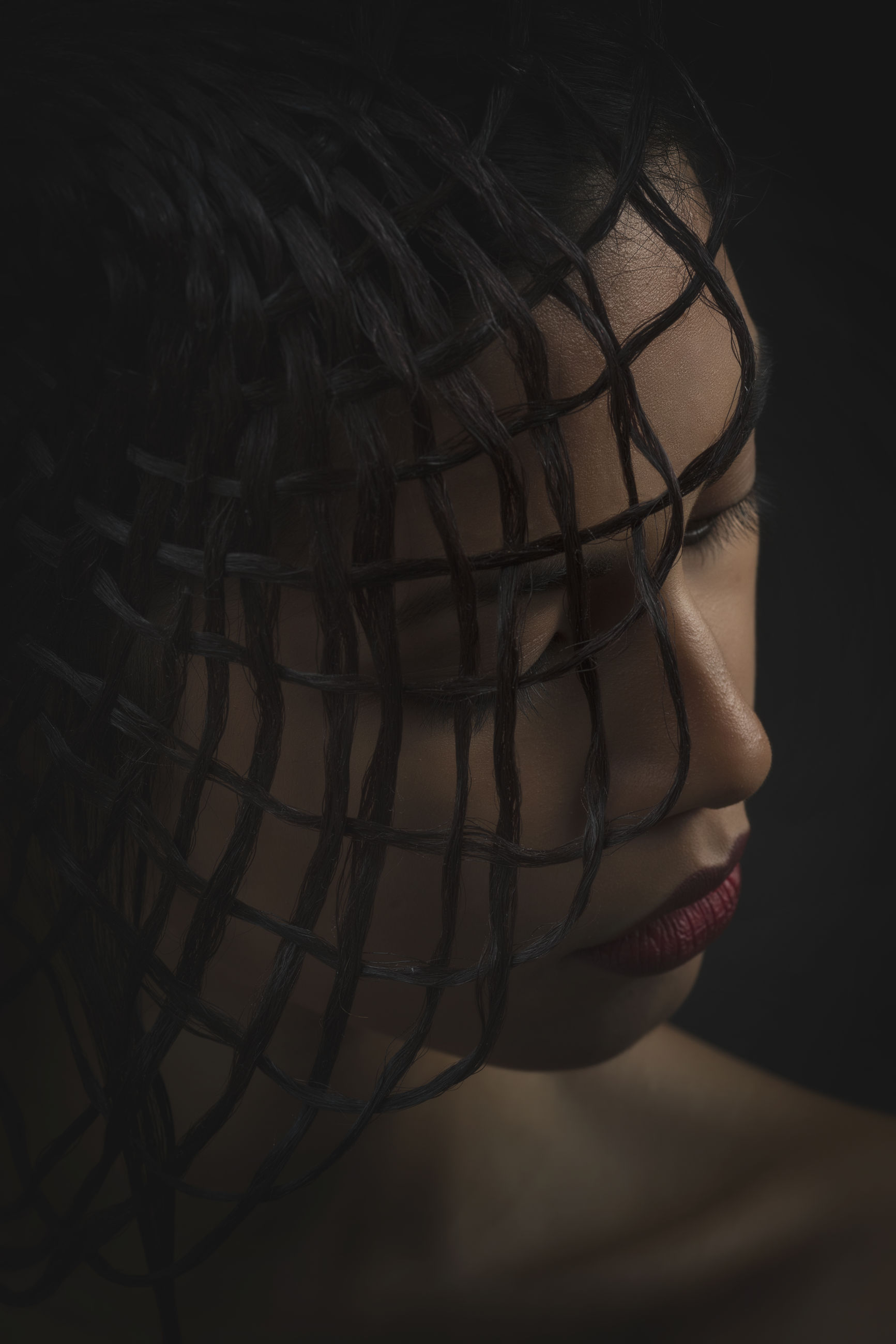 Close-up of young woman with hairstyle against black background