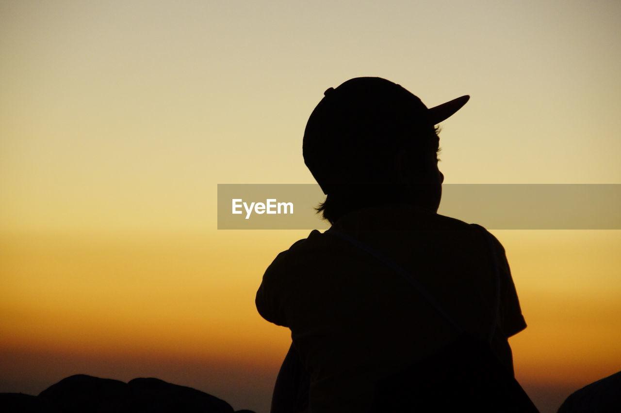 Silhouette boy standing against orange sky