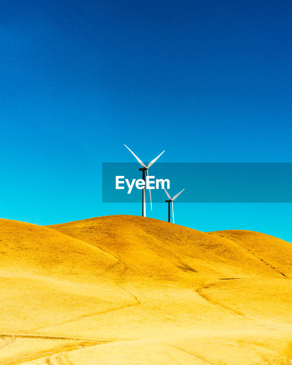 Windmill on desert against clear blue sky