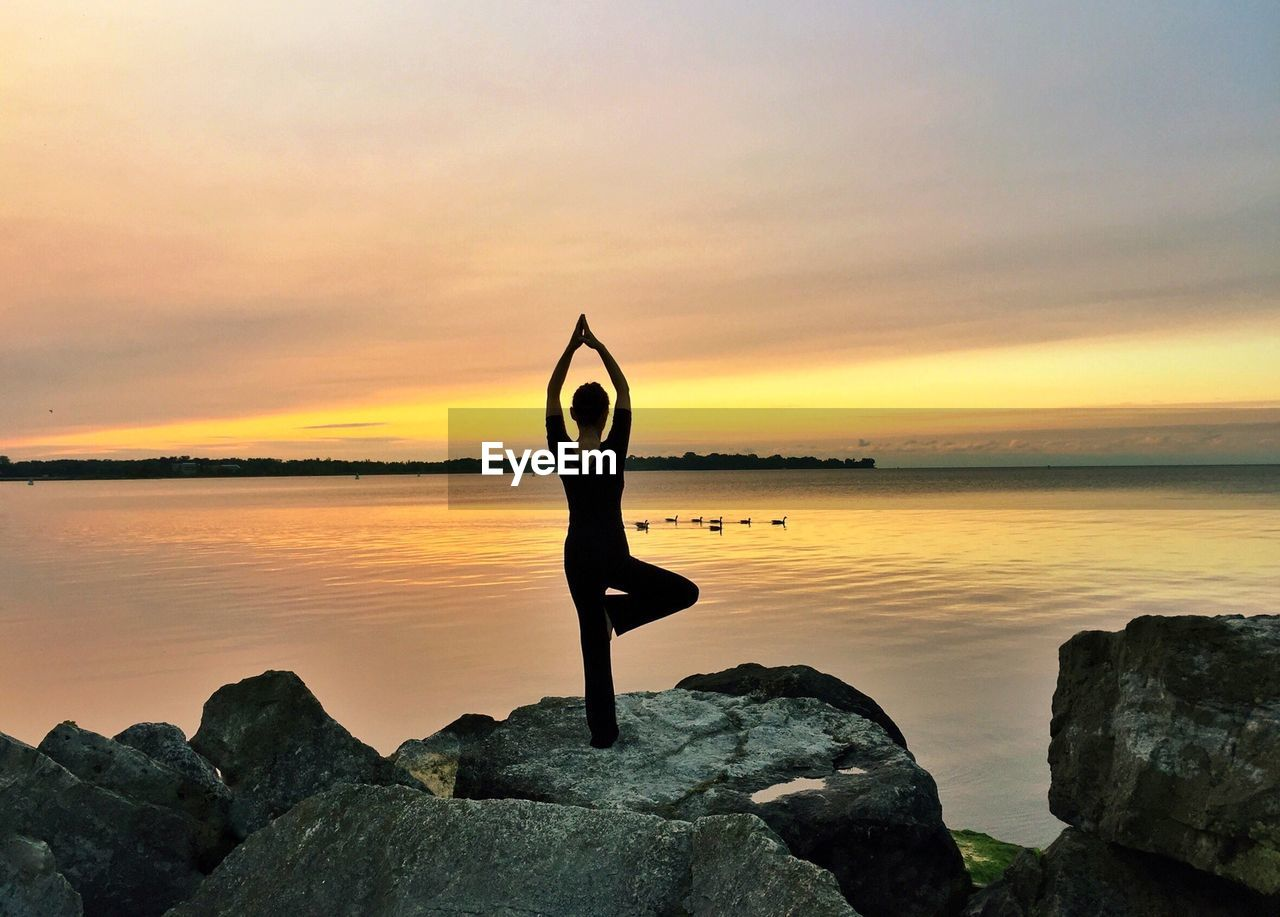 sky, sunset, water, rock, rock - object, solid, beauty in nature, lifestyles, sea, one person, orange color, wellbeing, leisure activity, yoga, relaxation exercise, exercising, scenics - nature, real people, tranquility, horizon over water, arms raised, human arm