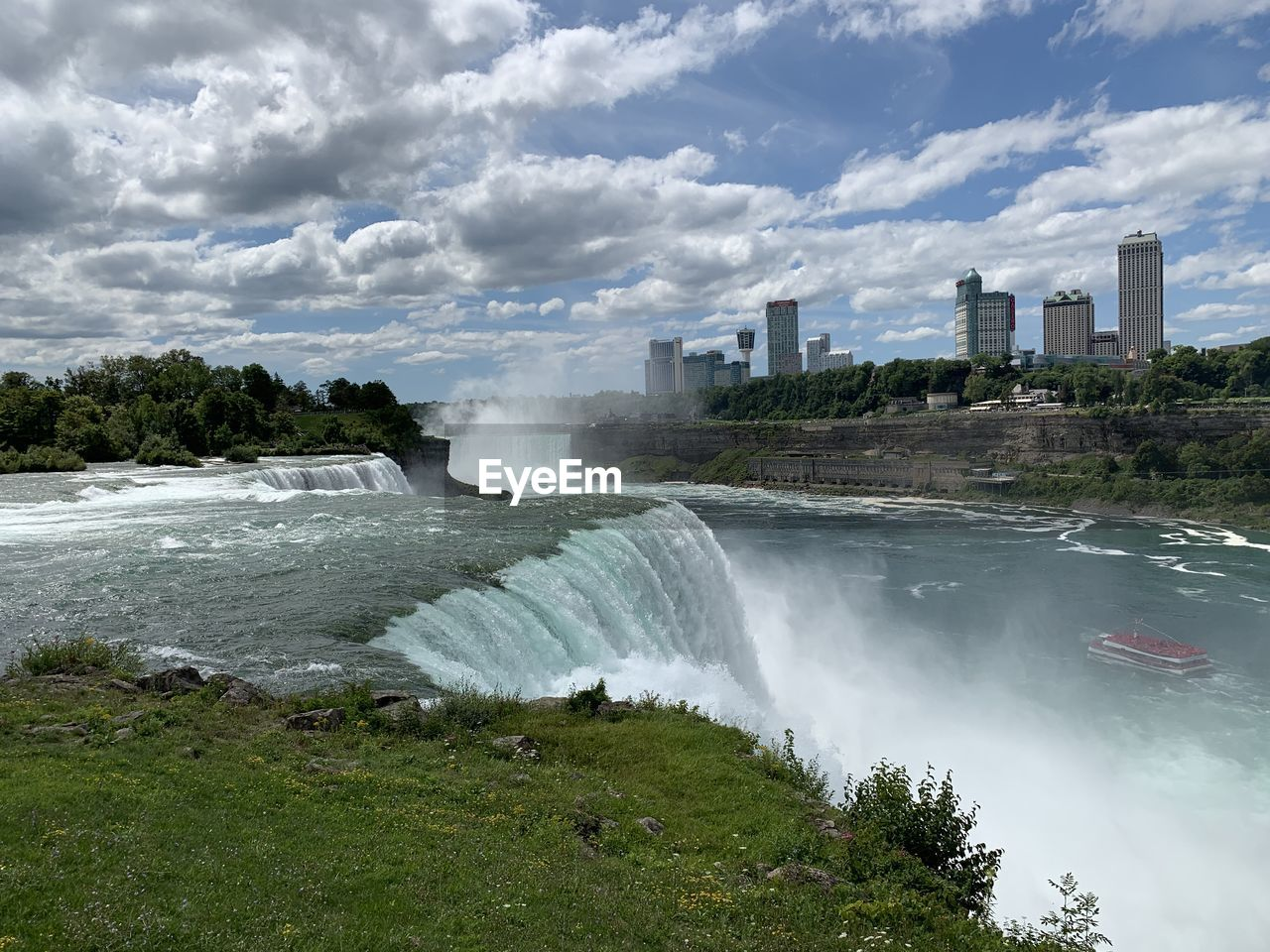 SCENIC VIEW OF WATERFALL BY CITY AGAINST SKY