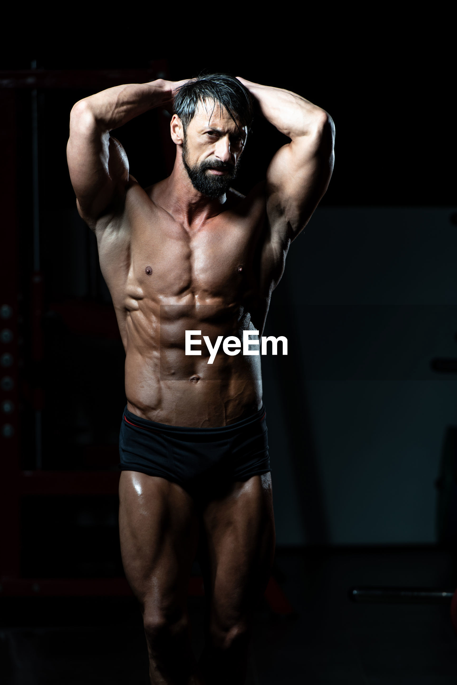 MIDSECTION OF SHIRTLESS MAN STANDING IN DARK