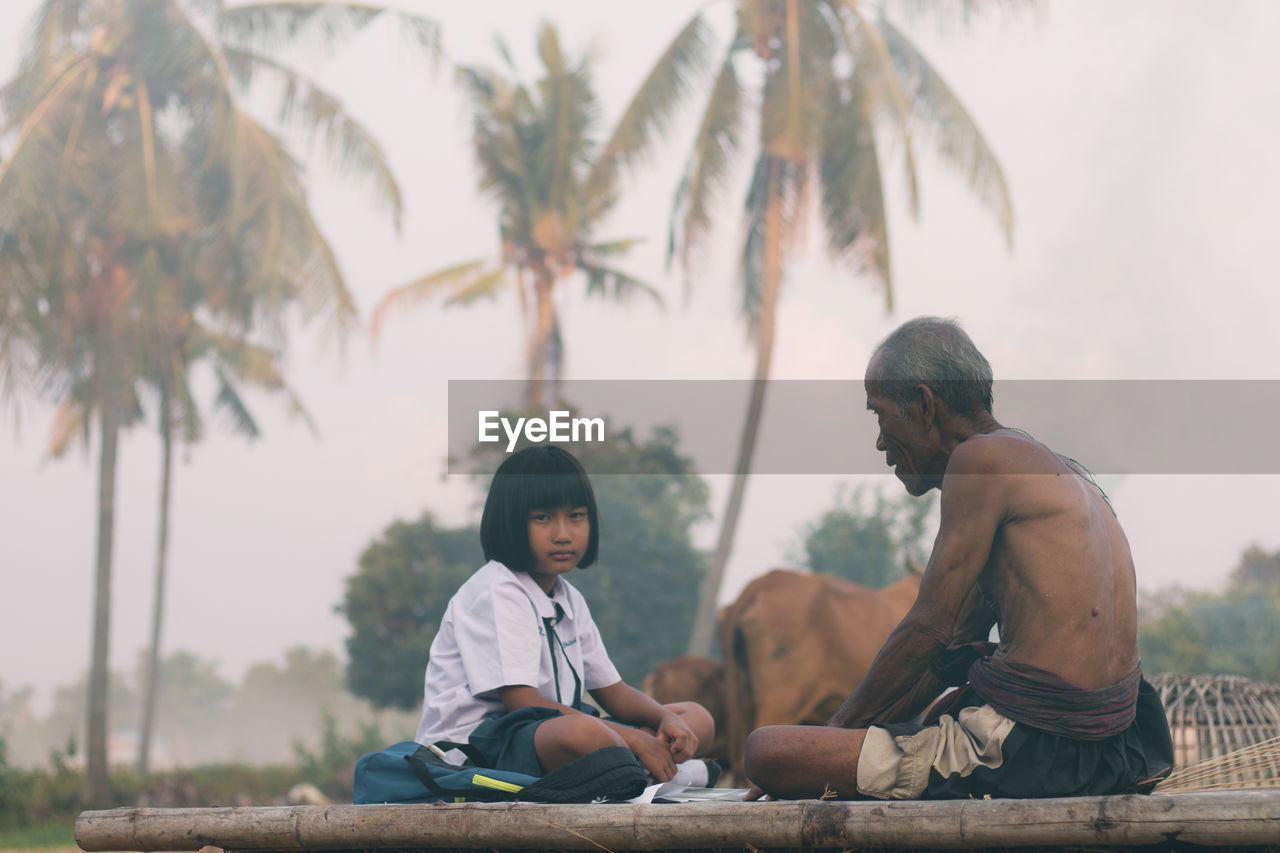 Portrait of girl sitting with shirtless grandfather against trees
