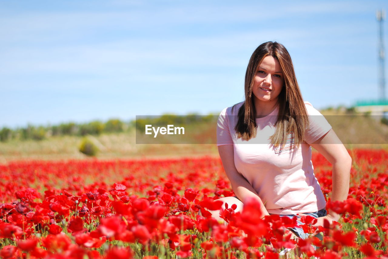 Young Woman Crouching Amidst Red Tulips On Field Against Sky During Sunny Day