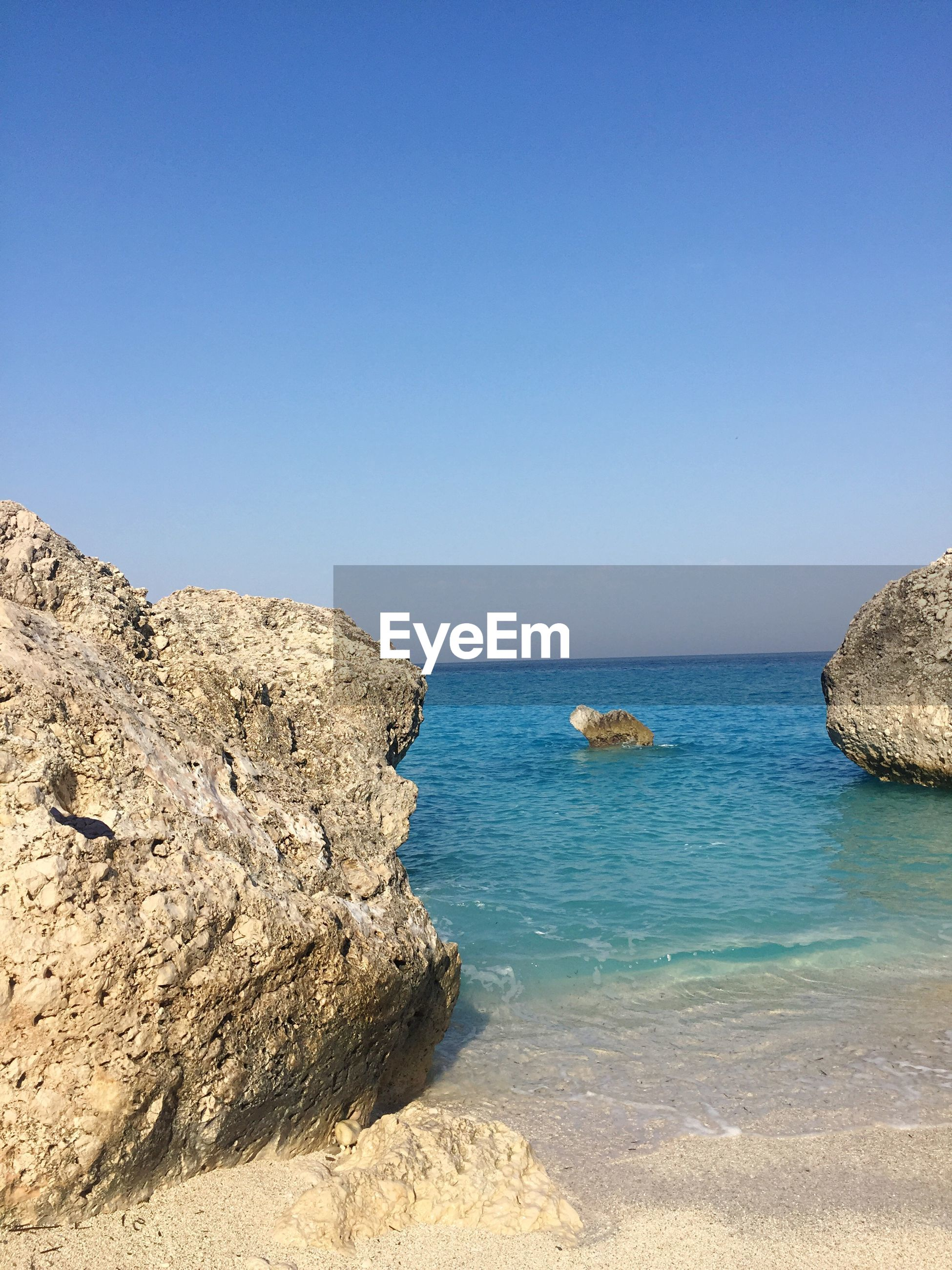 SCENIC VIEW OF ROCKS ON SEA AGAINST CLEAR BLUE SKY