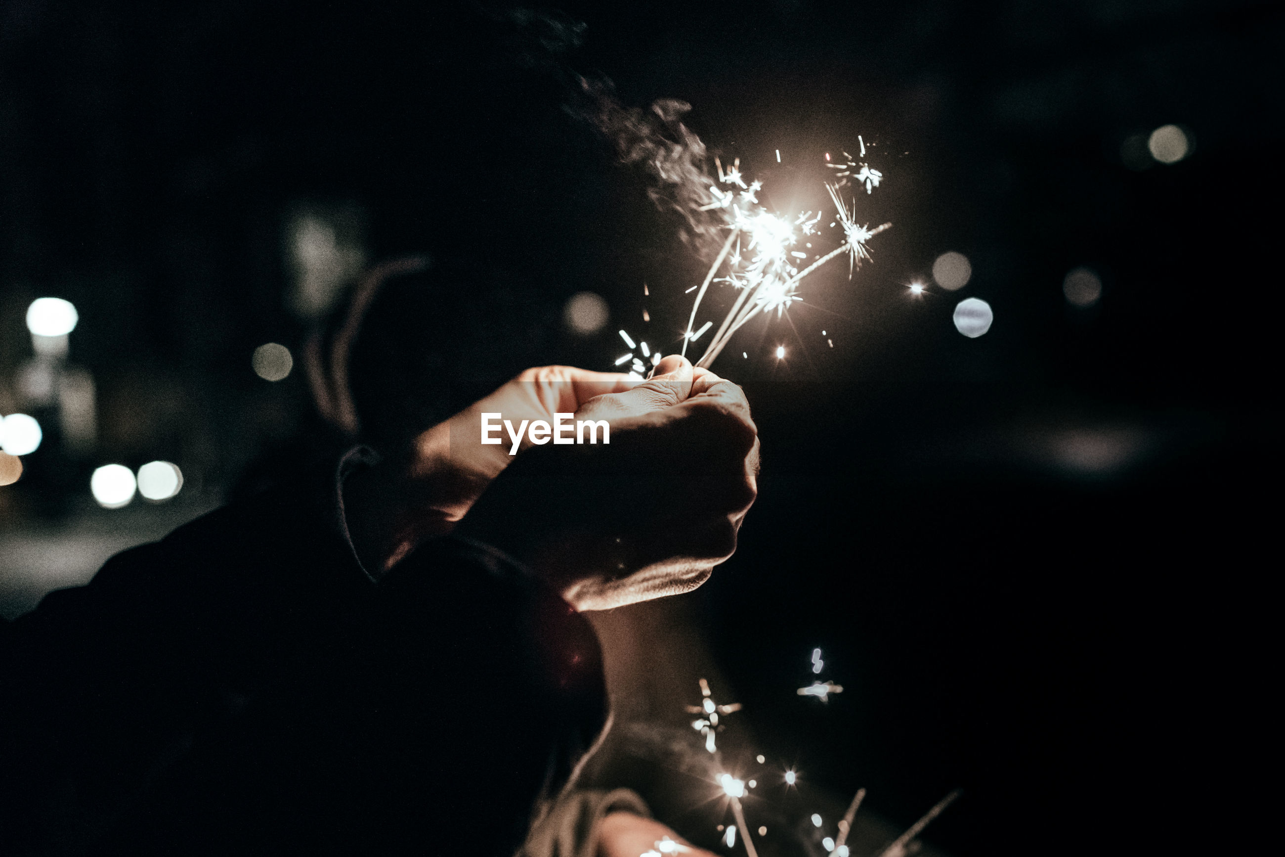 Close-up of man holding sparklers