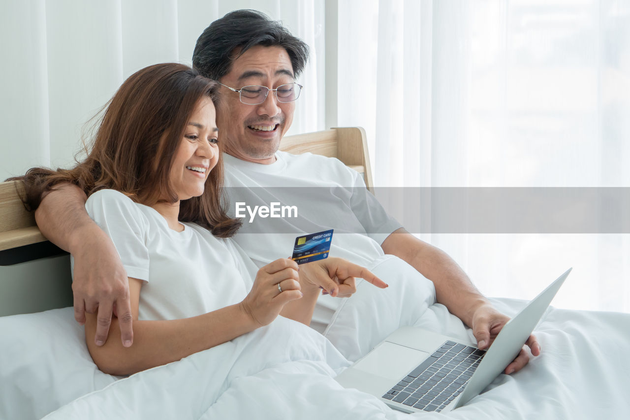 Happy couple shopping through laptop in bedroom