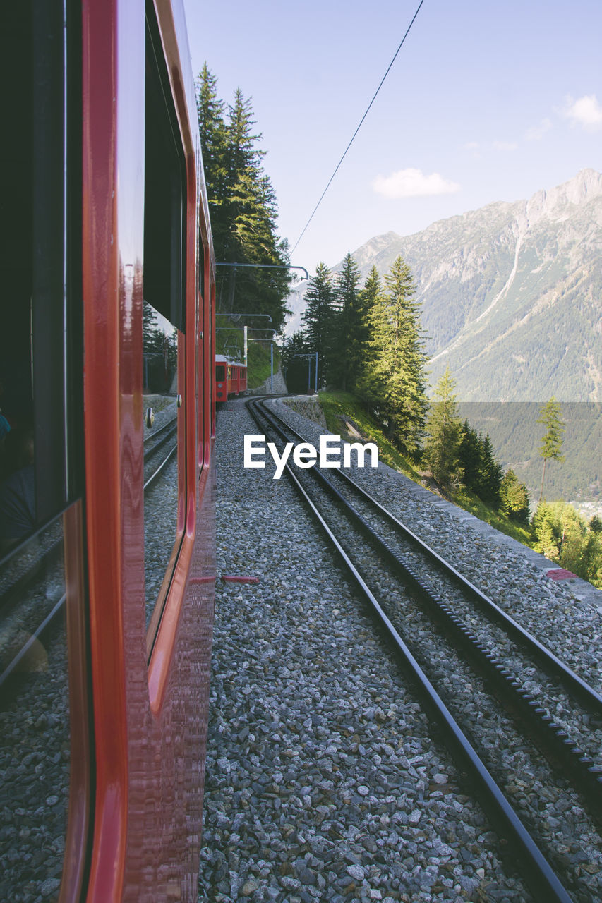TRAIN ON RAILROAD TRACK BY MOUNTAIN