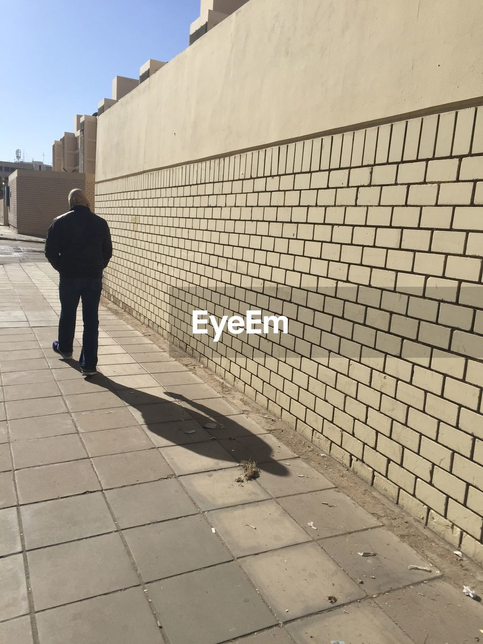 real people, one person, full length, rear view, architecture, men, lifestyles, walking, day, built structure, sunlight, leisure activity, footpath, nature, wall - building feature, shadow, standing, building exterior, city, outdoors