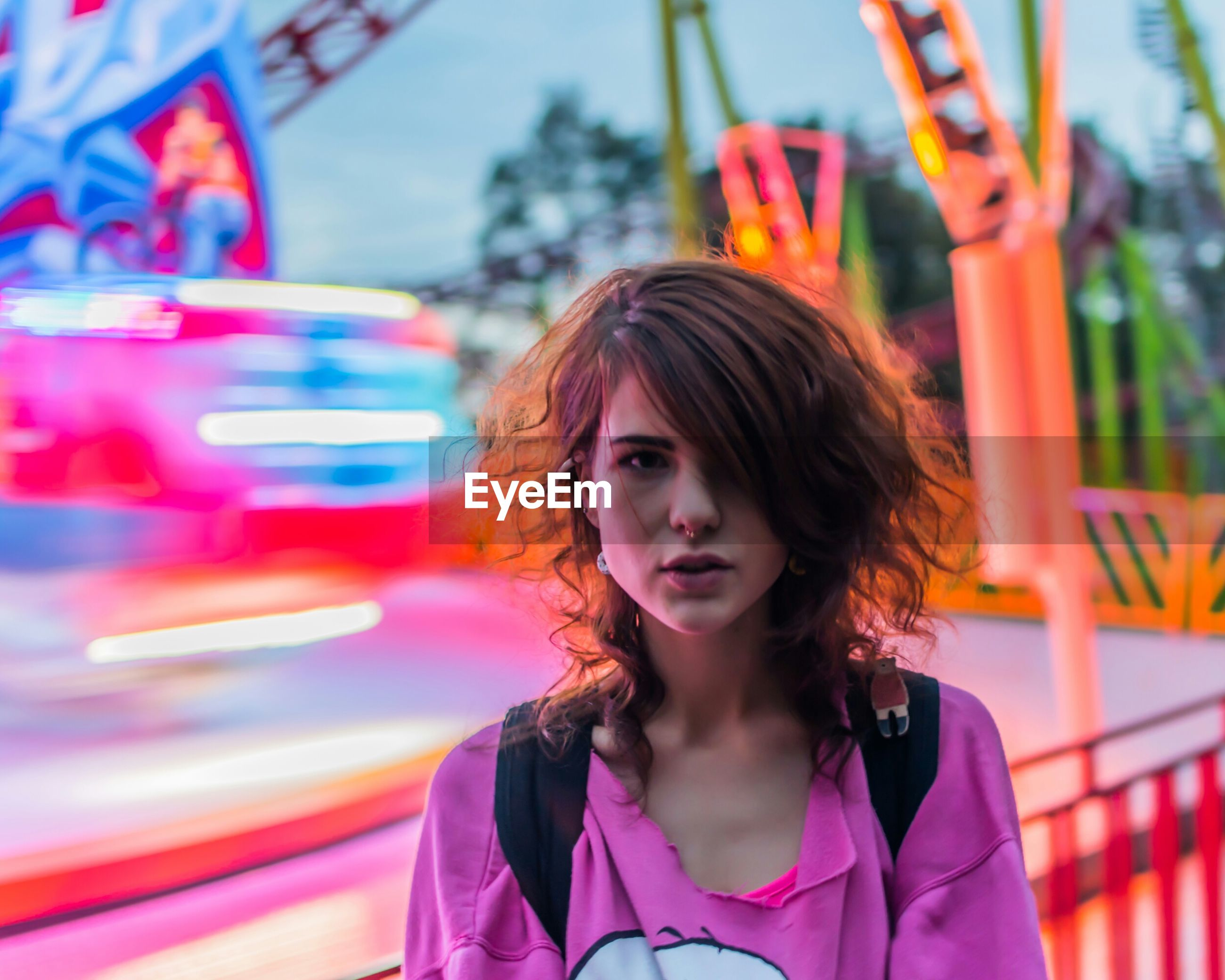 Portrait of young woman standing in amusement park