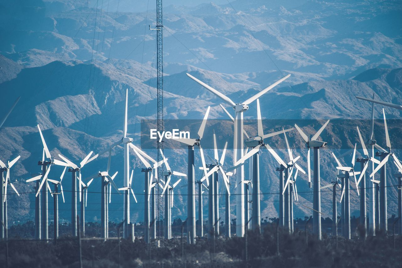 Wind Turbines On Land Against Sky