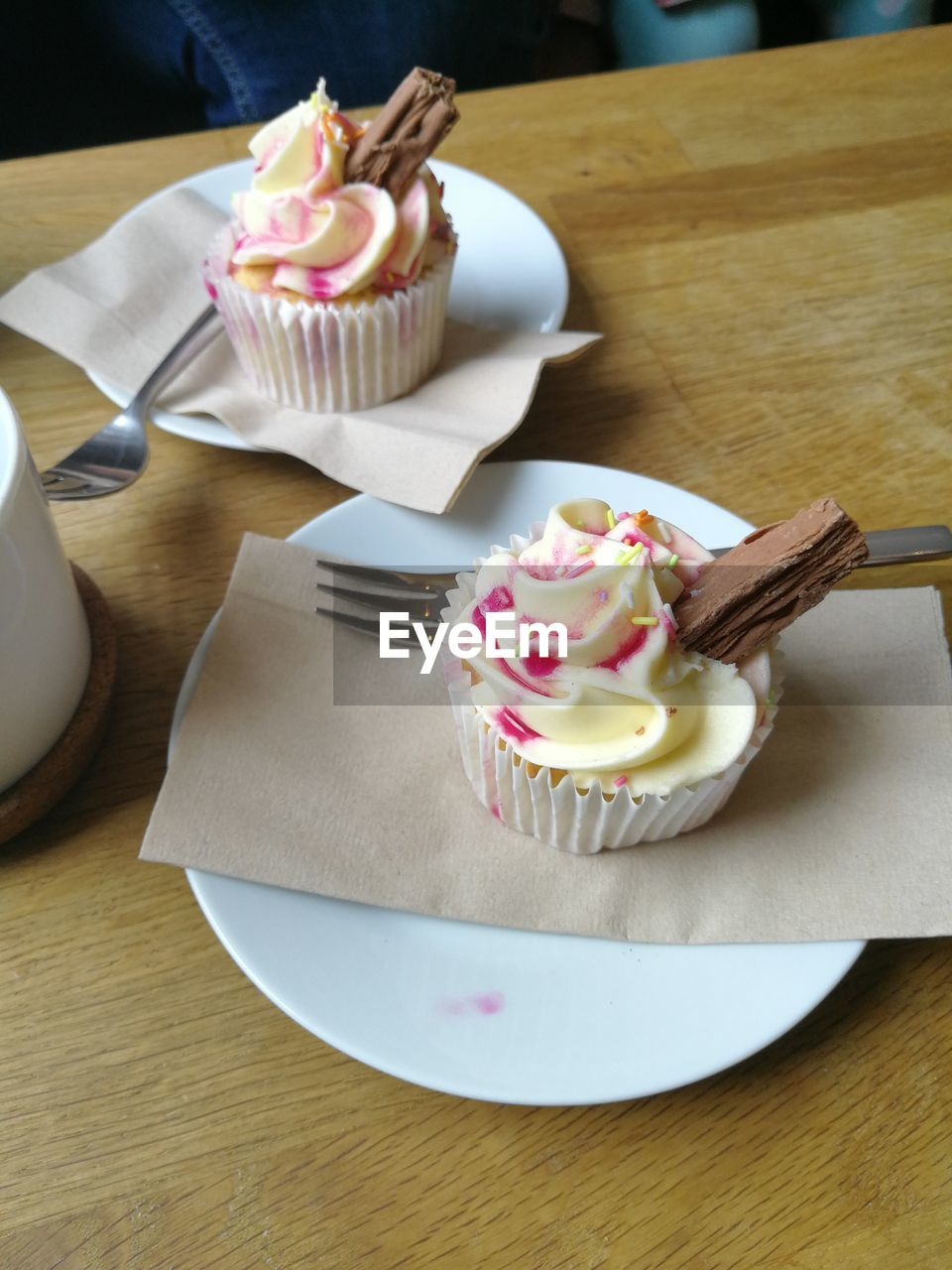 sweet food, cupcake, food and drink, dessert, table, indulgence, food, unhealthy eating, temptation, sprinkles, freshness, wood - material, indoors, cake, whipped cream, ready-to-eat, no people, plate, high angle view, serving size, cream, close-up, day