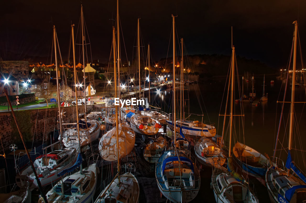 transportation, nautical vessel, night, mode of transportation, sailboat, illuminated, moored, water, mast, no people, pole, harbor, nature, arts culture and entertainment, architecture, outdoors, large group of objects, sea, built structure, port