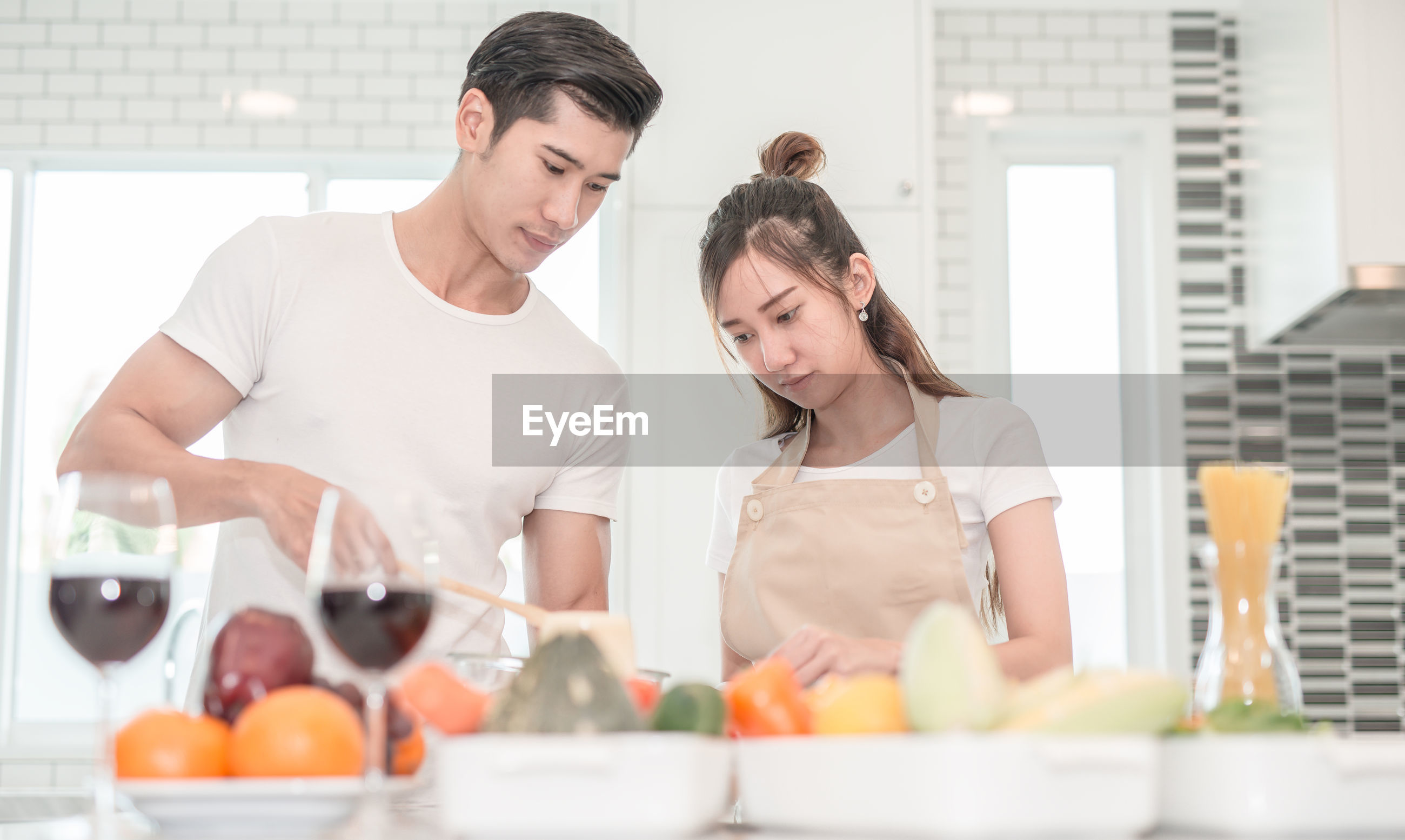 Young couple preparing food in kitchen at home