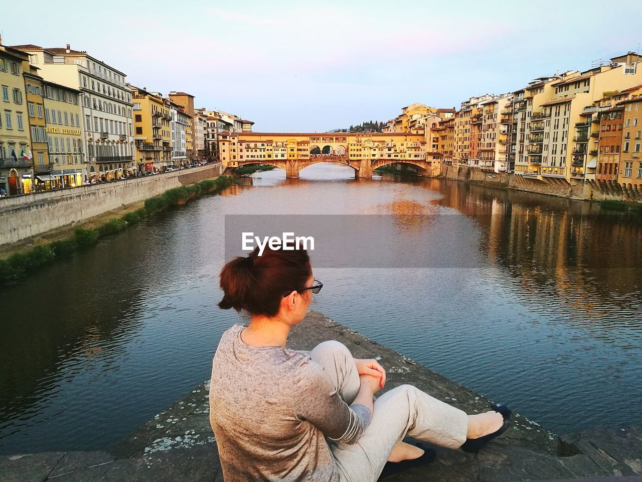 Woman Sitting By Arno River Against Ponte Vecchio