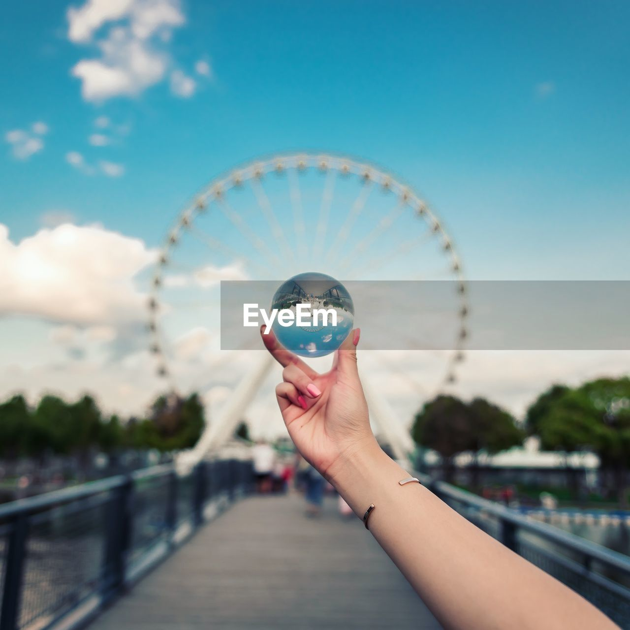 human hand, human body part, hand, real people, focus on foreground, built structure, ferris wheel, one person, leisure activity, sky, lifestyles, architecture, holding, nature, amusement park ride, day, unrecognizable person, city, body part, finger, outdoors, nail
