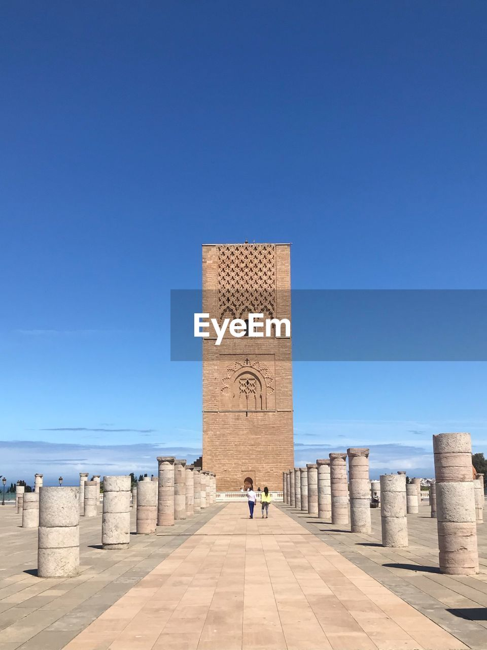architecture, sky, clear sky, history, the past, built structure, blue, copy space, sunlight, day, nature, travel destinations, building exterior, building, tourism, travel, incidental people, real people, tower, one person, outdoors, architectural column, ancient civilization