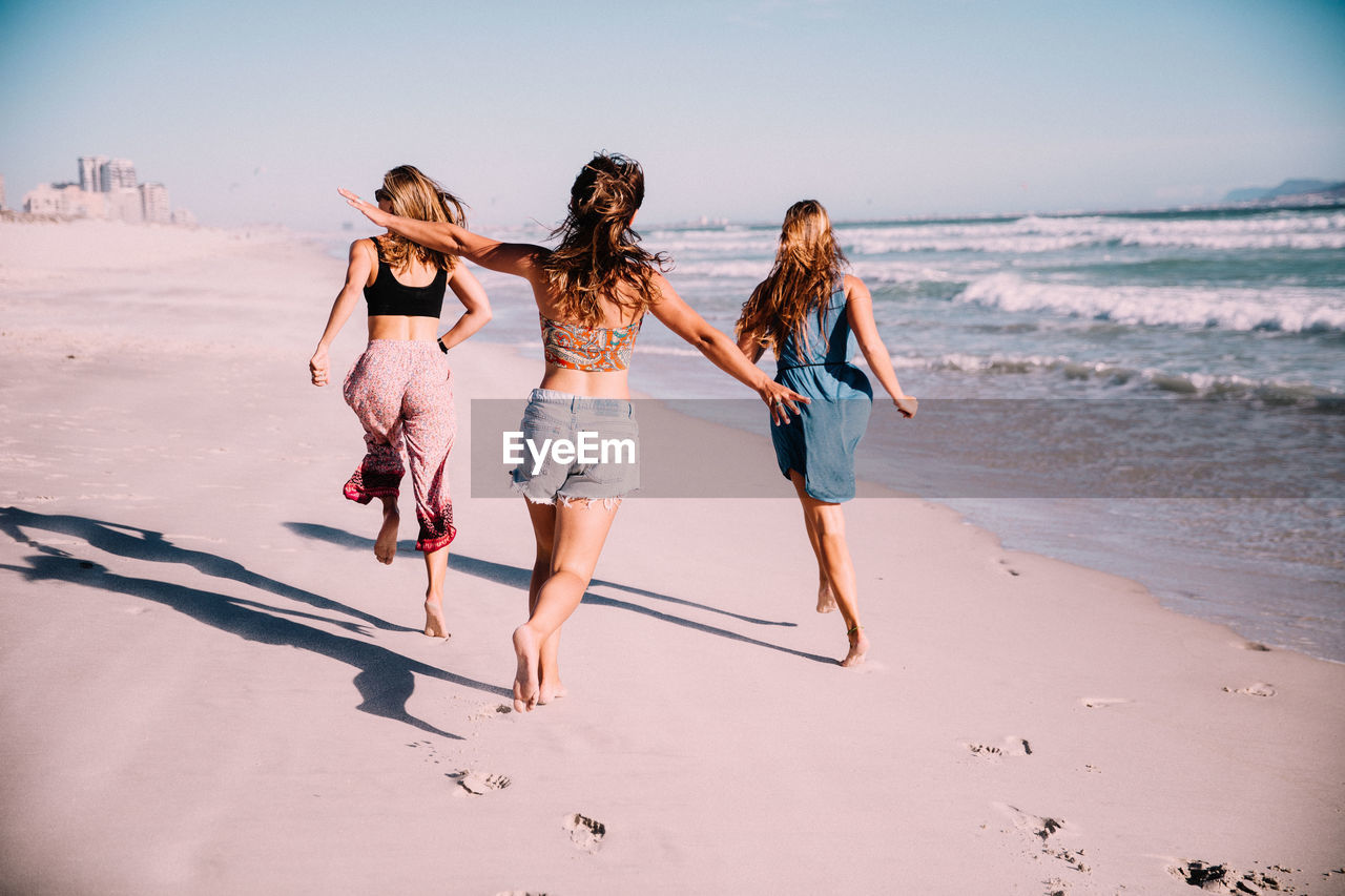 beach, land, full length, leisure activity, lifestyles, togetherness, real people, women, water, sea, sand, sky, rear view, nature, walking, friendship, beauty in nature, people, clothing, horizon over water, outdoors, positive emotion