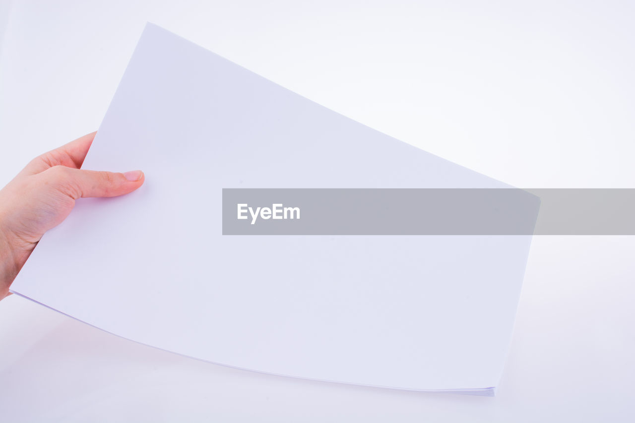Close-up of hand holding blank paper against white background