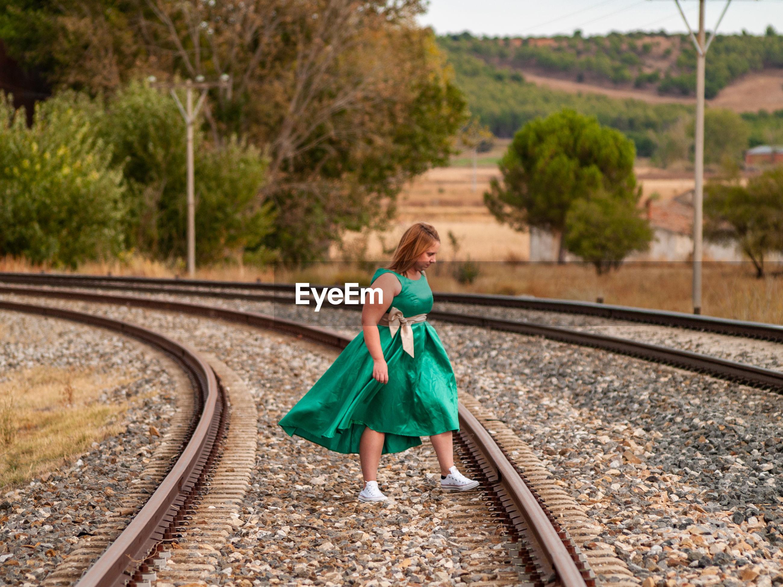 Woman standing on railroad tracks