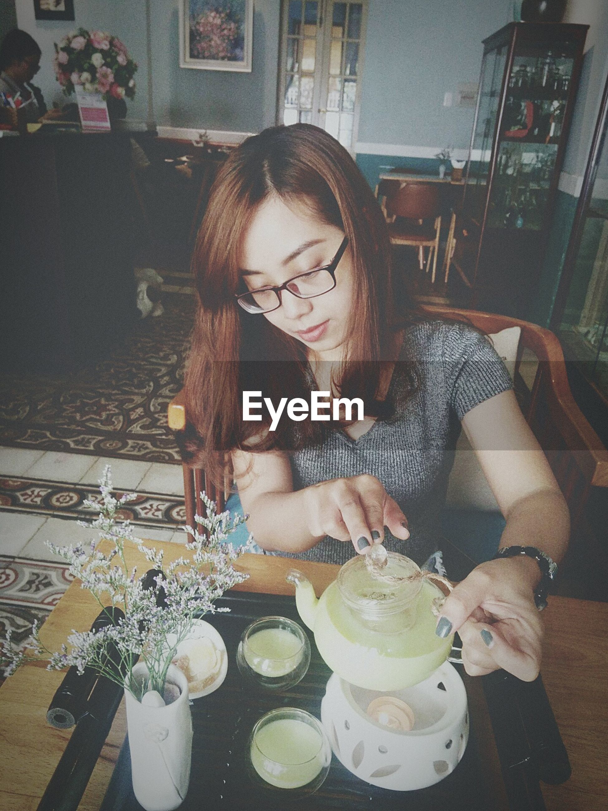 waist up, young adult, only women, table, eyeglasses, indoors, looking down, one person, one woman only, adults only, adult, young women, women, one young woman only, old-fashioned, food, dessert, people, drinking glass, portrait, time, day, human hand