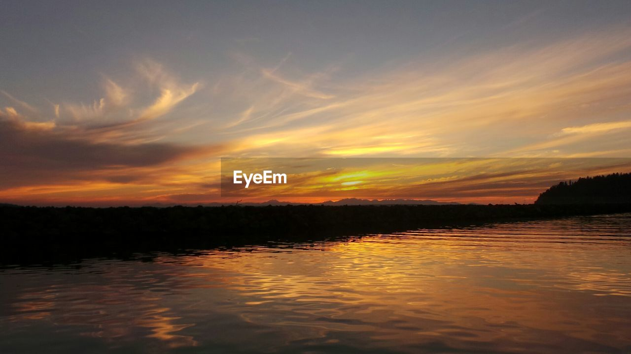 Scenic view of river against orange cloudy sky