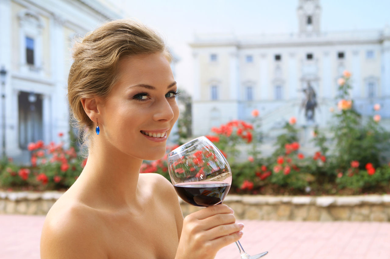 Close-Up Portrait Of Beautiful Woman Drinking Red Wine Against Building