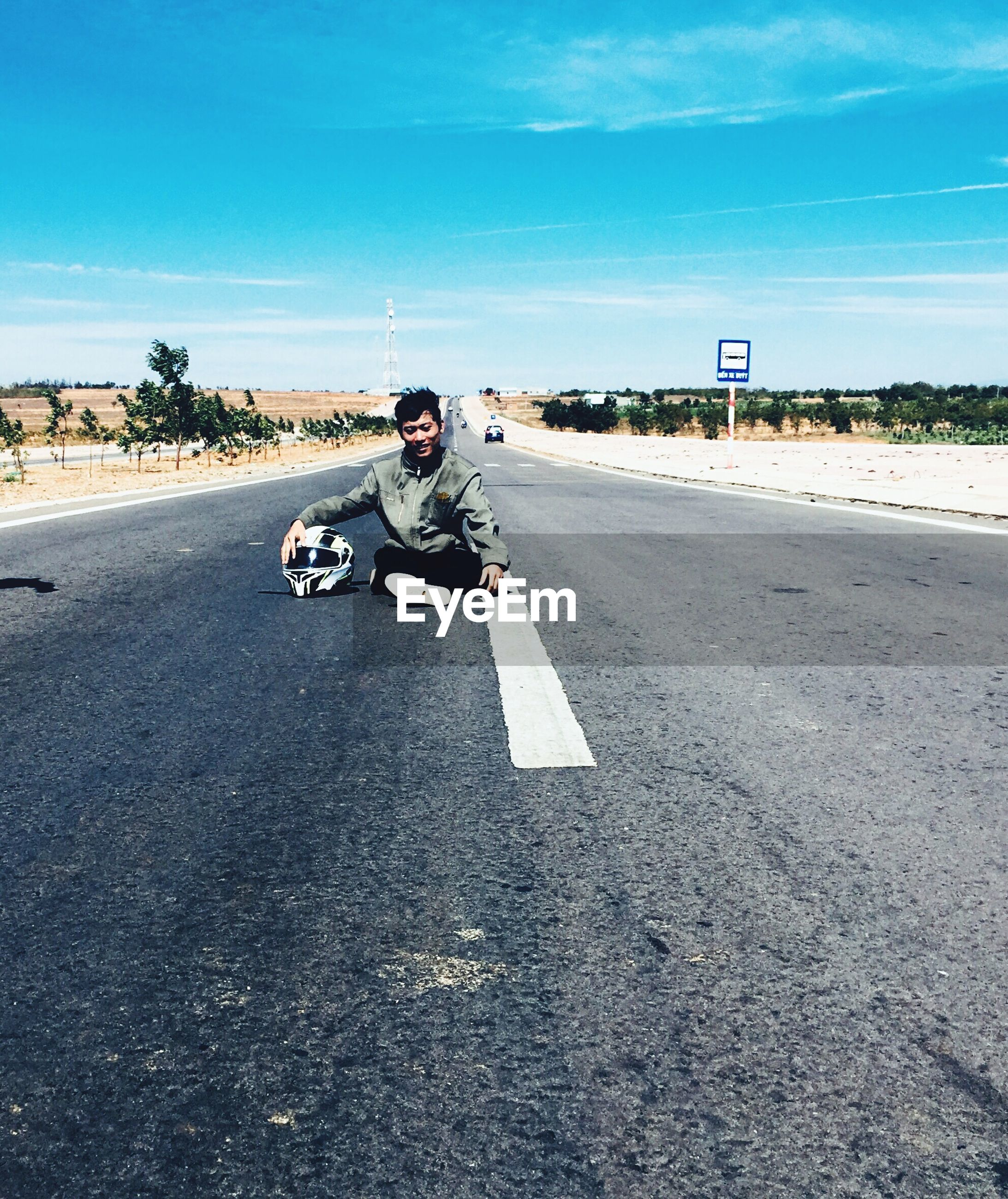 Man sitting on road against sky