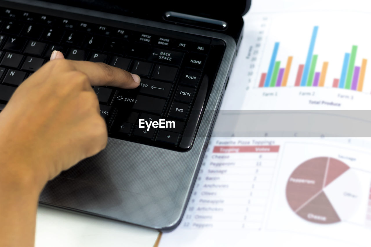 Cropped image of person using laptop on table