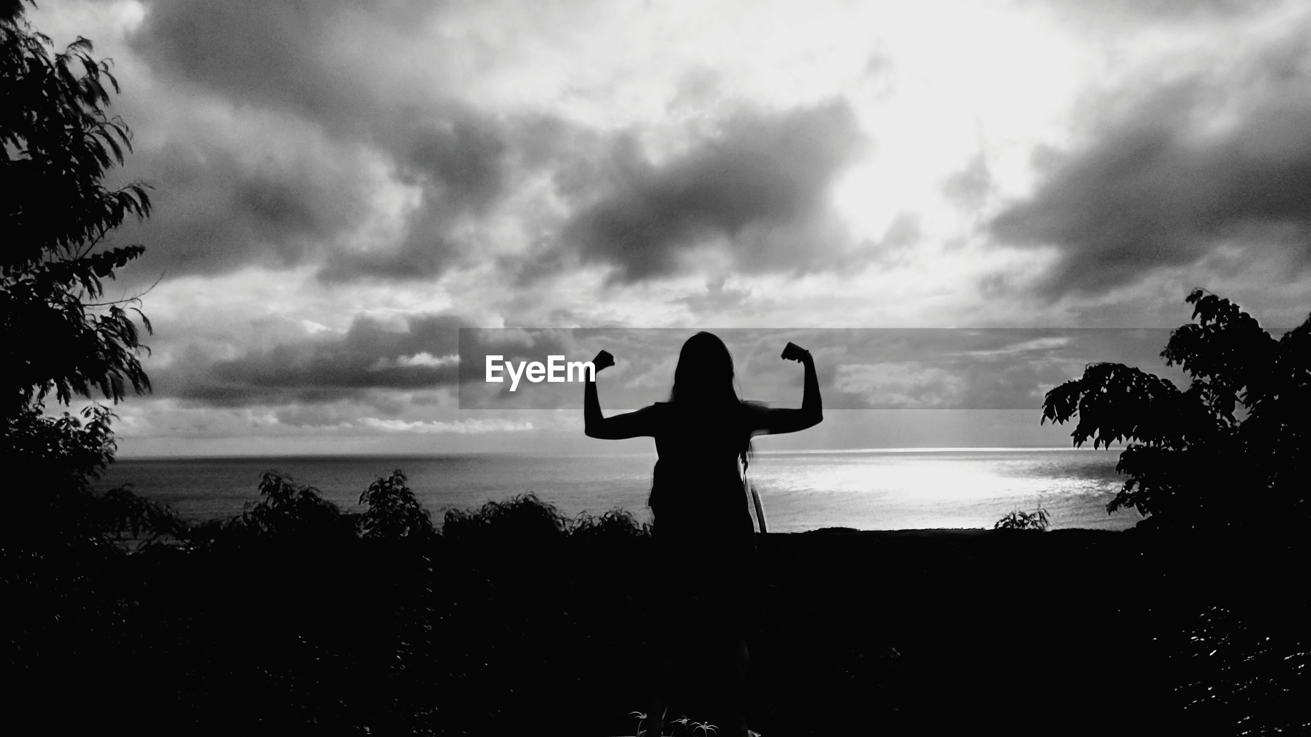 Silhouette of woman flexing muscles on field by sea against cloudy sky