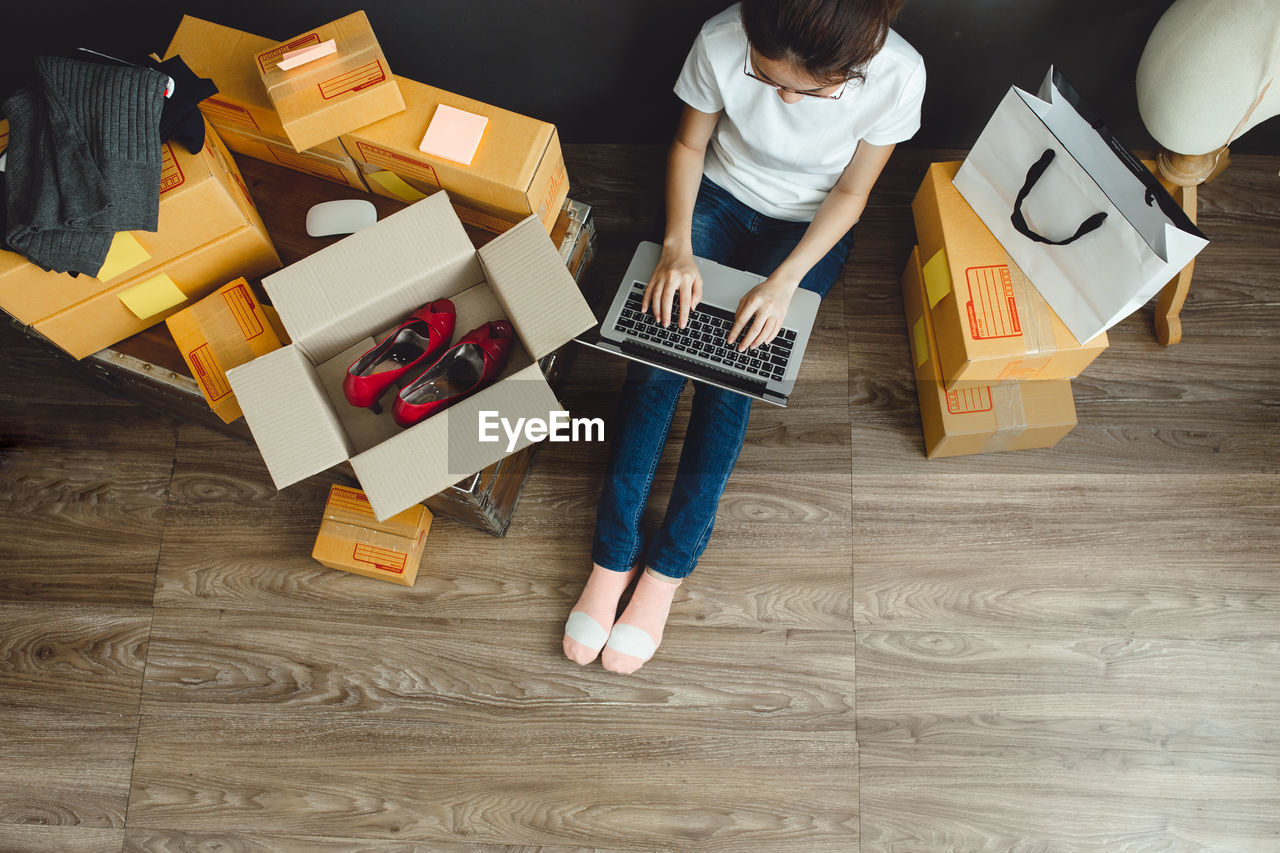 High angle view of woman using laptop while sitting by boxes on wooden floor