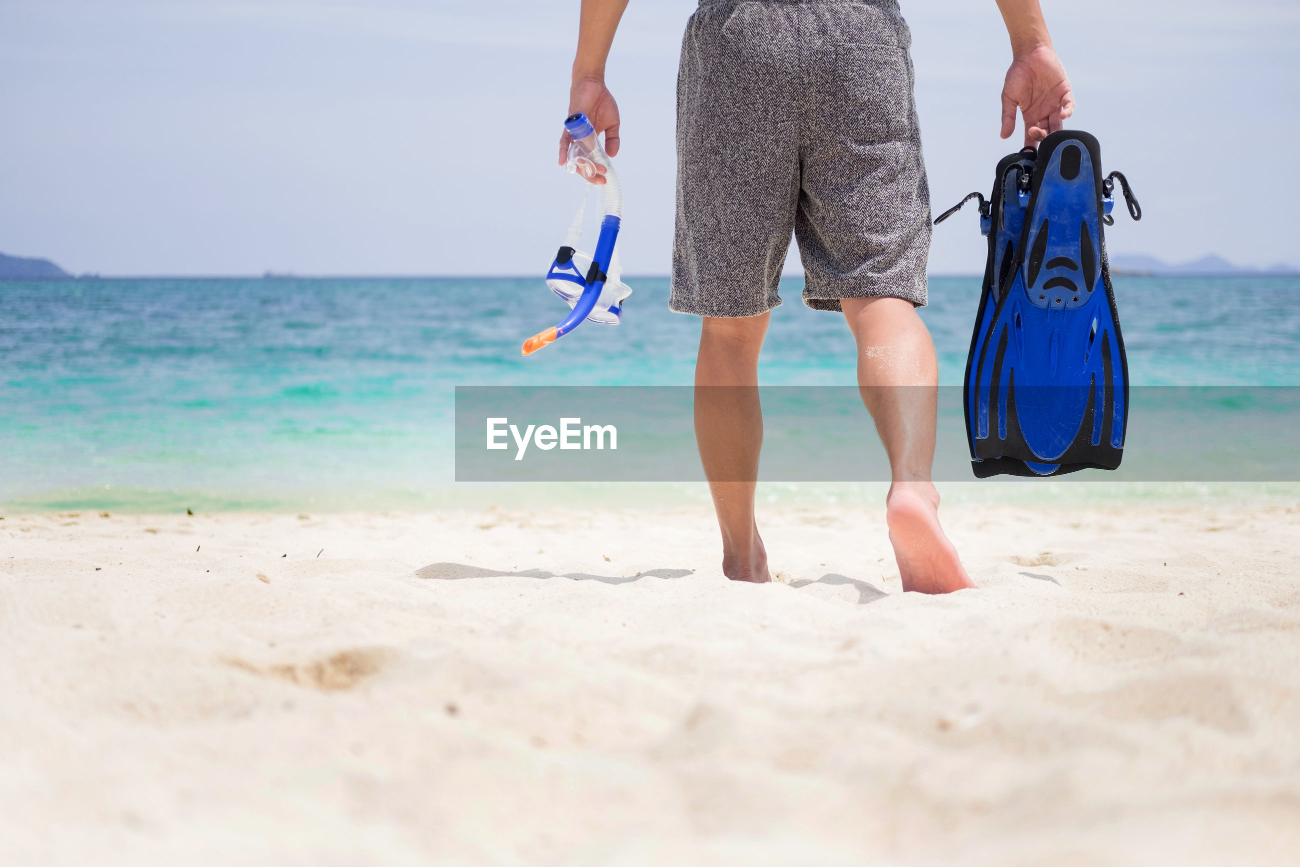 Low section of man with diving equipment walking towards sea at beach