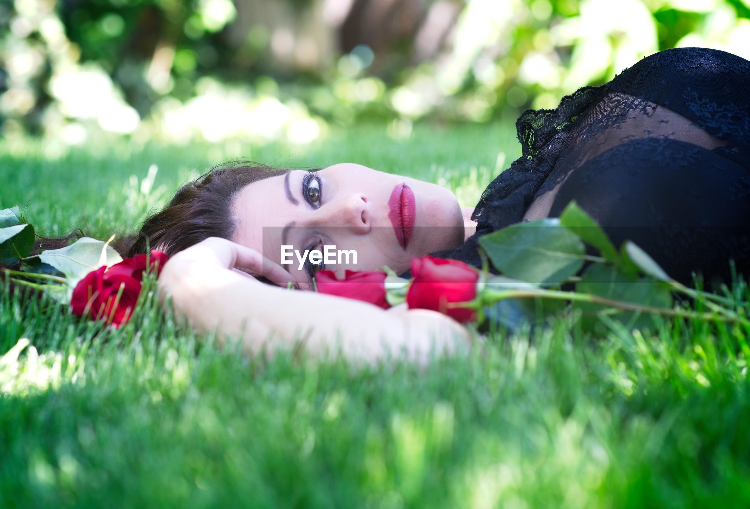 lying down, plant, portrait, grass, one person, looking at camera, leisure activity, real people, relaxation, nature, young adult, young women, lifestyles, selective focus, women, day, flower, flowering plant, beautiful woman, outdoors