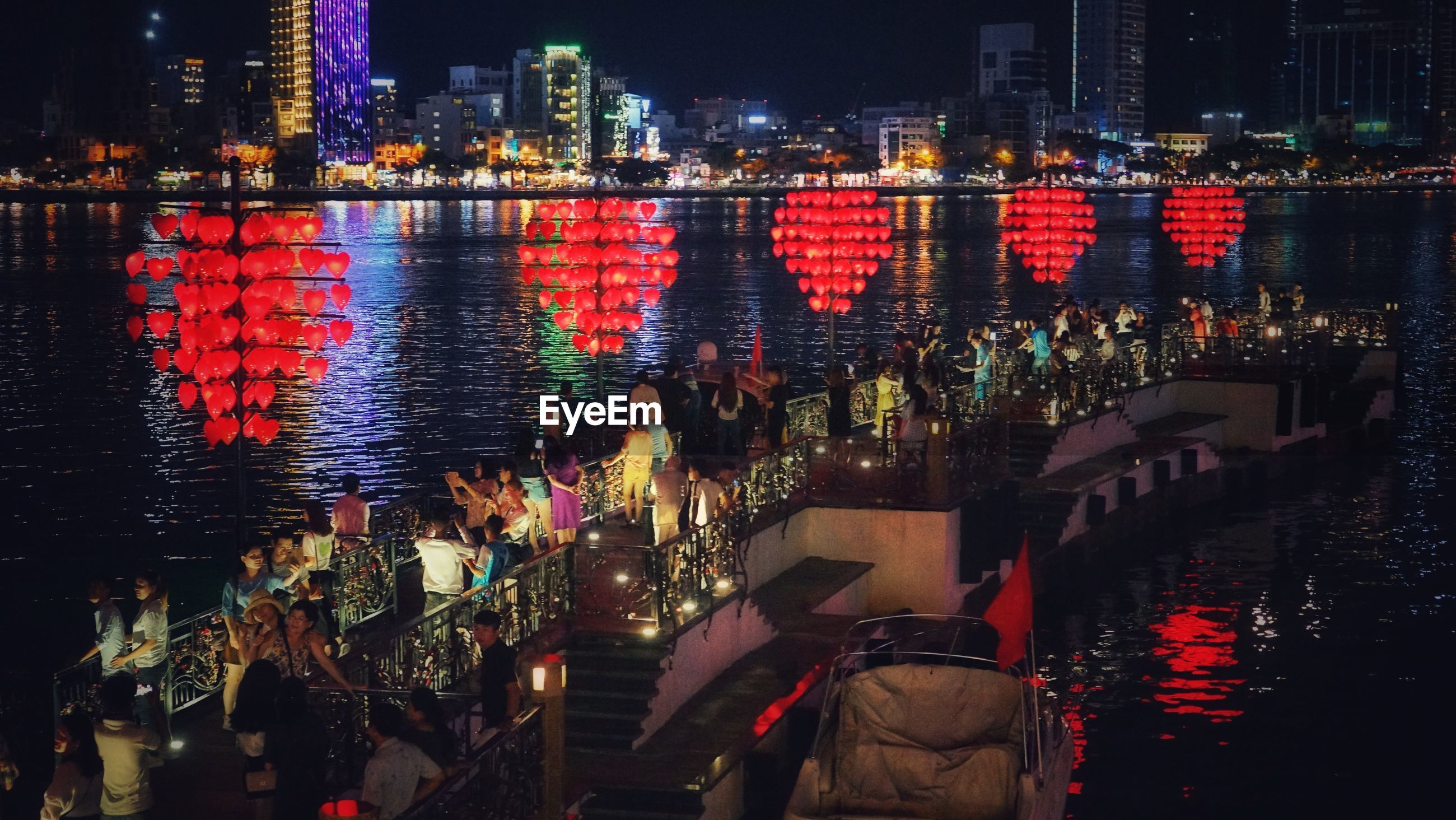 Panoramic view of crowd at illuminated city by river at night