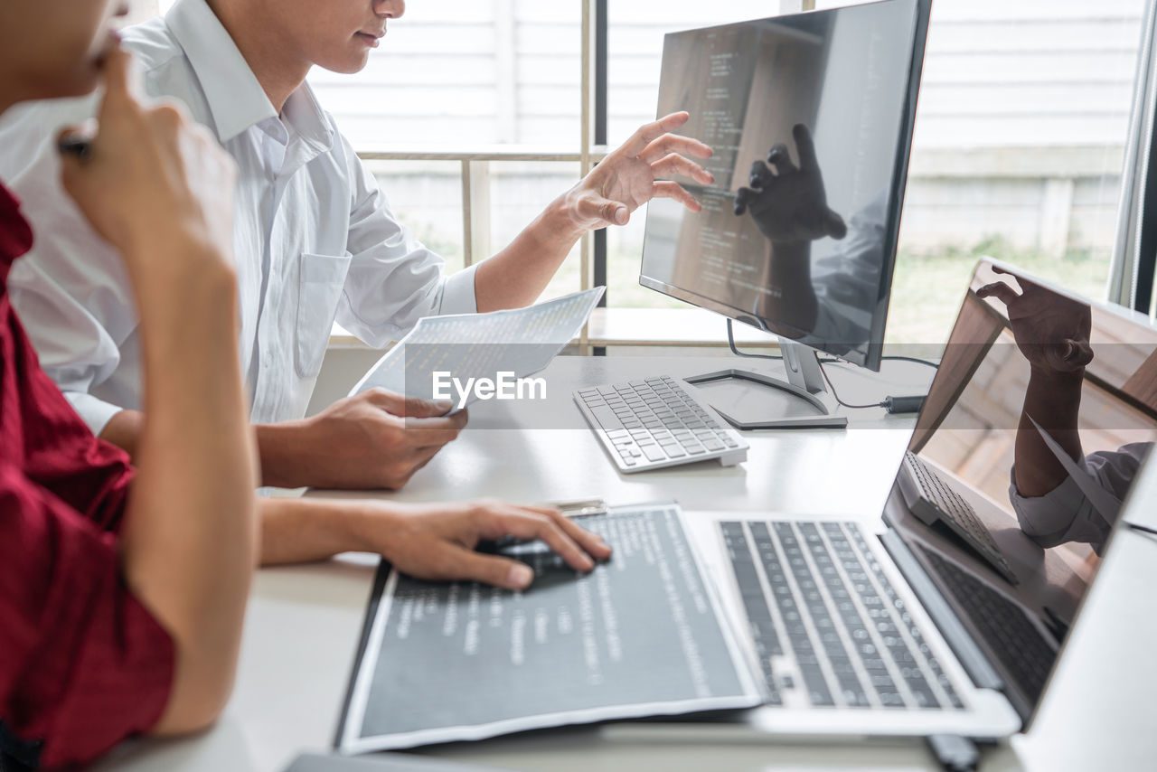 MIDSECTION OF WOMAN USING LAPTOP