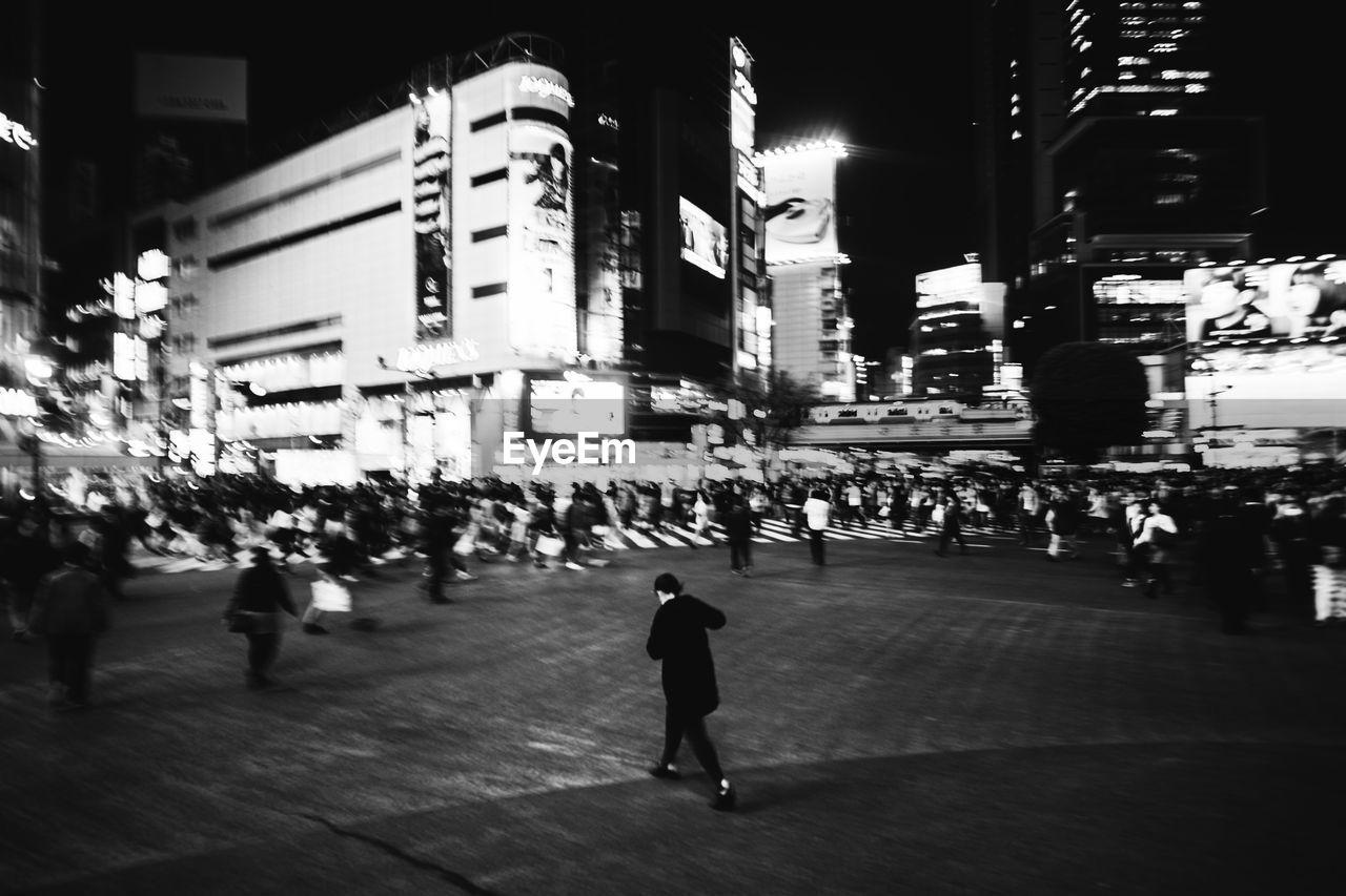 WOMAN STANDING ON ILLUMINATED CITY STREET