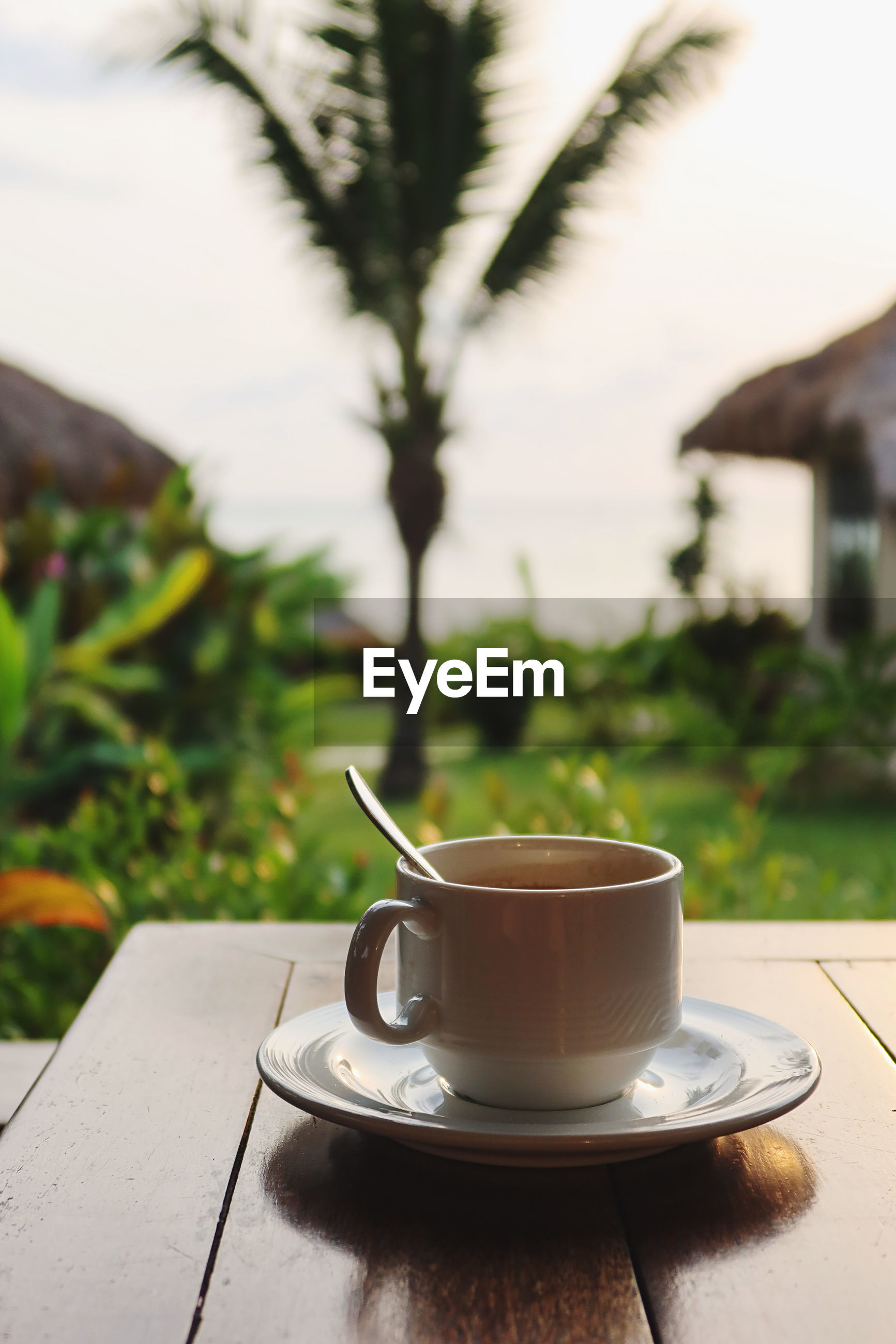 CLOSE-UP OF COFFEE CUP ON TABLE AGAINST BLURRED BACKGROUND