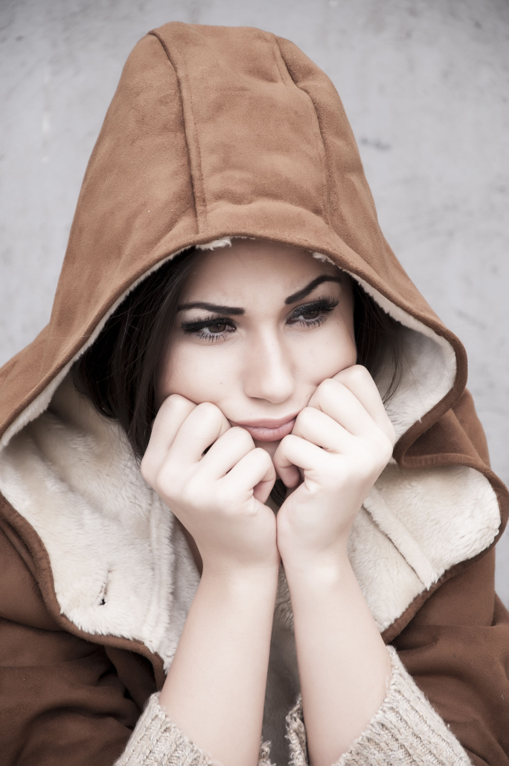 High angle view of sad thoughtful woman wearing warm clothing sitting outdoors