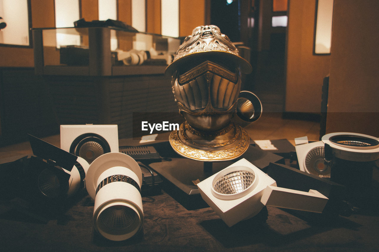 Close-up of ancient helmet and lighting equipment on table