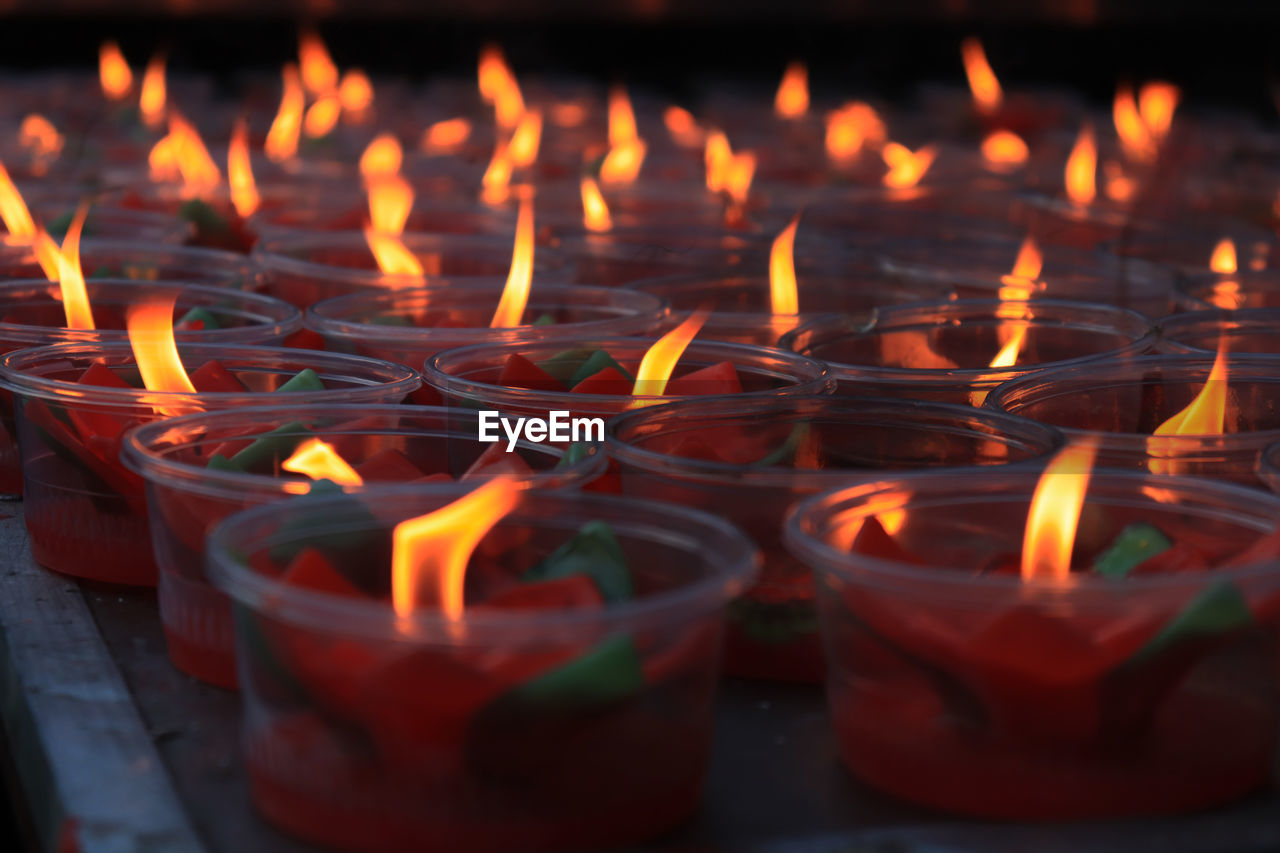 burning, fire, flame, heat - temperature, fire - natural phenomenon, illuminated, glowing, candle, religion, belief, spirituality, nature, place of worship, orange color, no people, large group of objects, lighting equipment, close-up, architecture, building, electric lamp