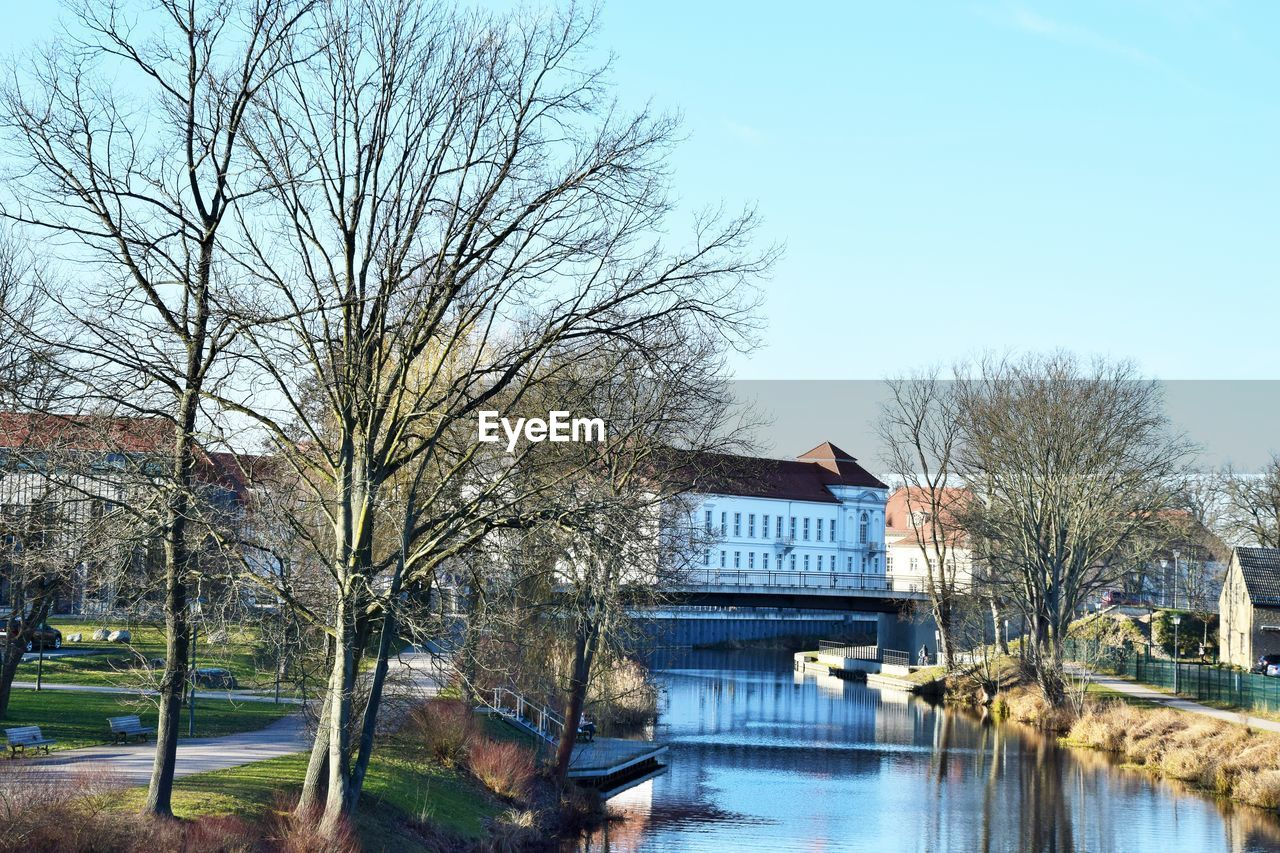 tree, architecture, built structure, water, building exterior, bare tree, sky, plant, nature, no people, day, building, reflection, river, residential district, house, outdoors, bridge, waterfront
