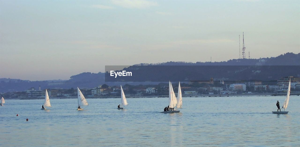 water, waterfront, nautical vessel, sky, transportation, sea, sailboat, mode of transportation, nature, day, scenics - nature, beauty in nature, outdoors, mountain, travel, sailing, motion, sport, tranquil scene