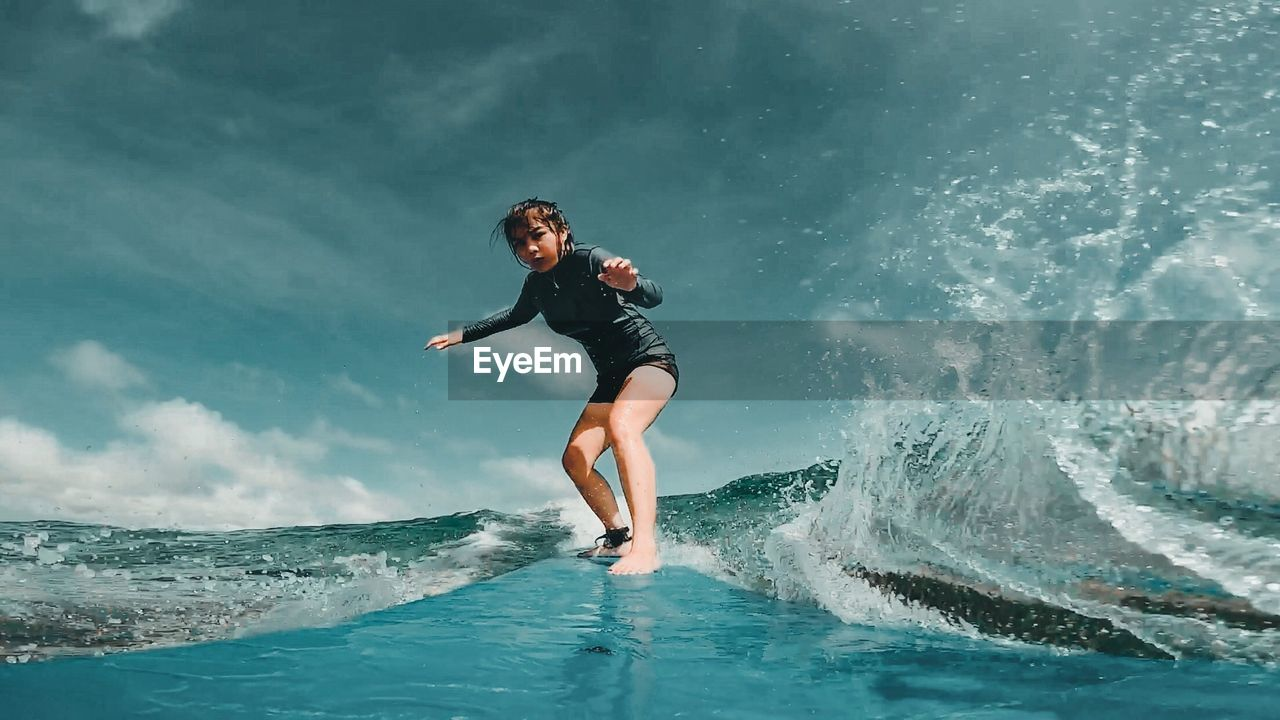 Young Woman Surfing On Sea Against Sky