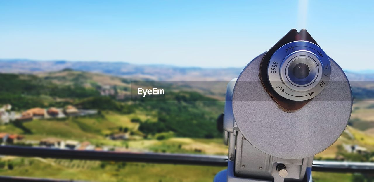 coin operated, focus on foreground, binoculars, sky, coin-operated binoculars, day, nature, telescope, optical instrument, no people, close-up, landscape, security, technology, metal, environment, outdoors, surveillance, clear sky, scenics - nature, astronomy, hand-held telescope