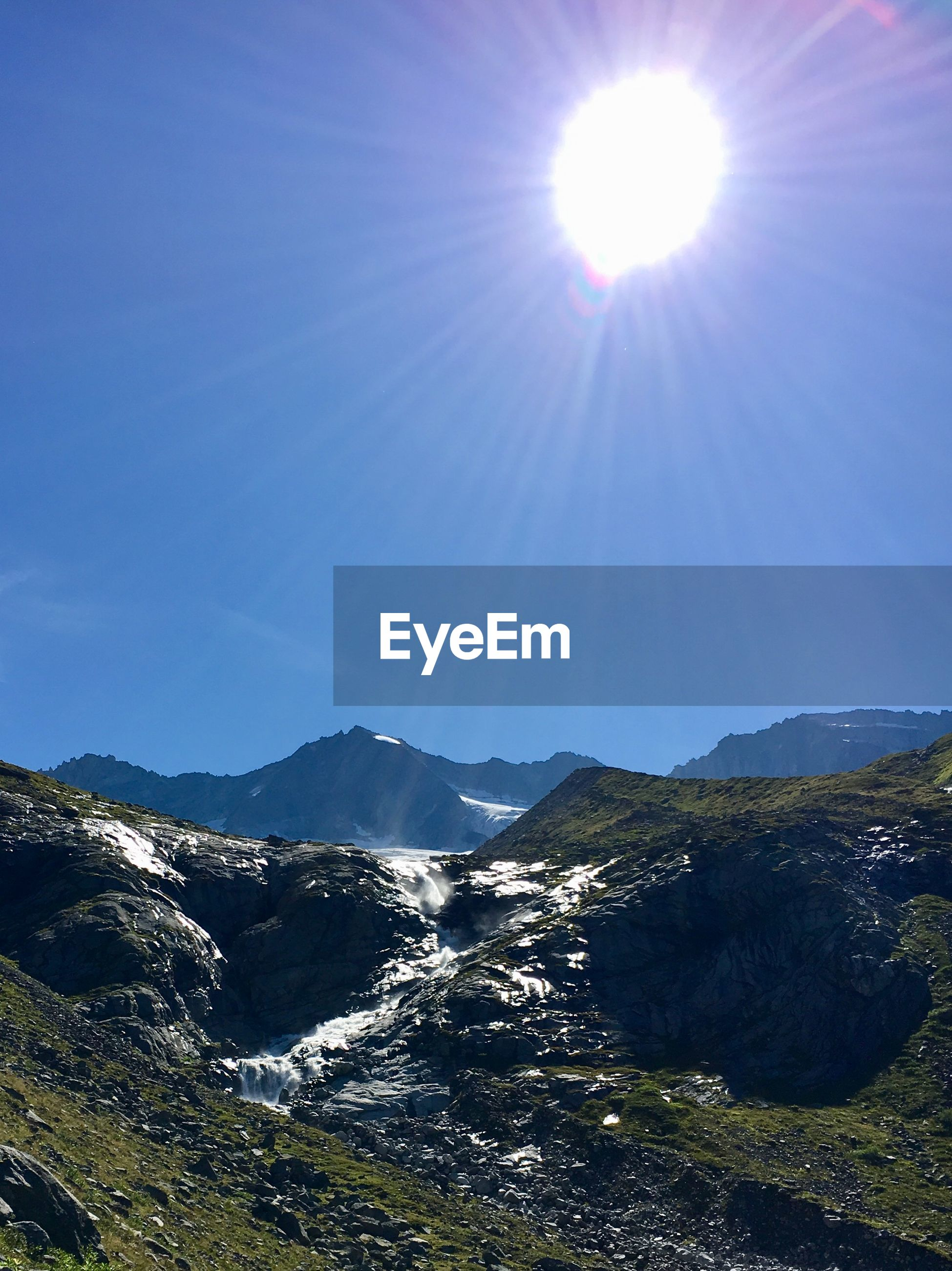 Scenic view of mountains against sky on sunny day