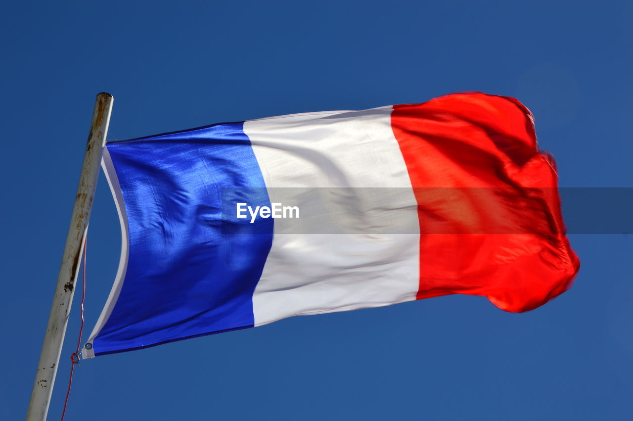 Low angle view of french flag against blue sky