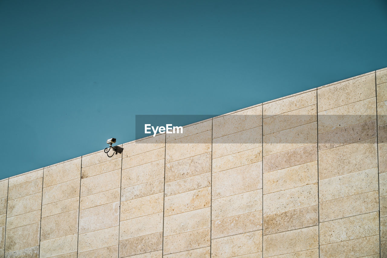 architecture, built structure, blue, building exterior, real people, men, day, sky, wall - building feature, nature, low angle view, one person, copy space, building, outdoors, sunlight, lifestyles, clear sky, wall, concrete
